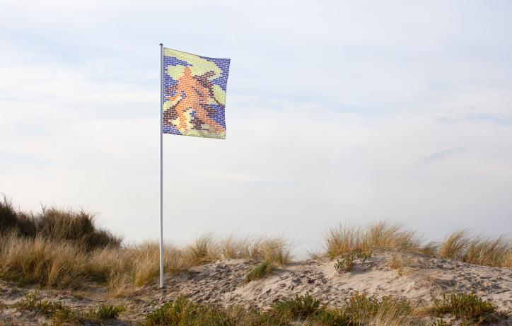 Campagnebeeld Festival van de Architectuur. Een vlag op een vlaggenmast in de duinen. Beeld gemaakt door Telma Lannoo en Tom Callemin